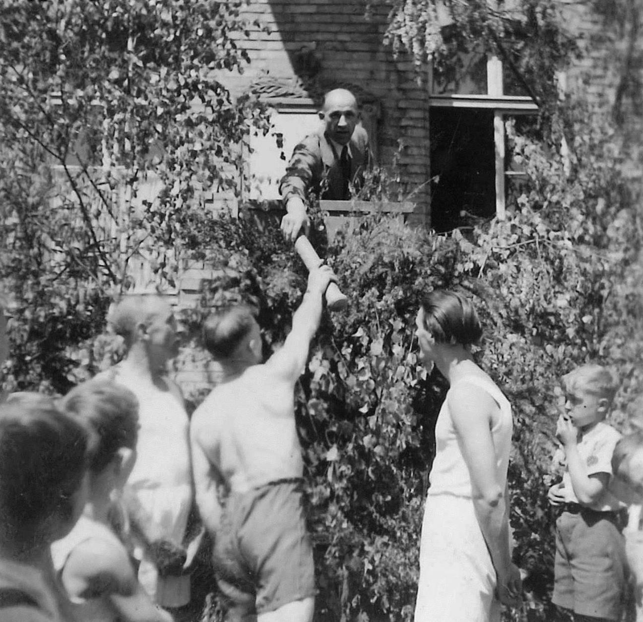 Ludwig Schulmeyer, Vorsitzender der Sport- und Kulturvereinigung (SKV), übergibt die Mörfelder Grußbotschaft einem Stafettenläufer, der sie direkt zur Feier der Wiedereröffnung der Frankfurter Paulskirche bringt. Mörfelden, 18. Mai 1948
